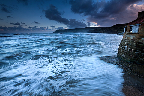 North Sea waves crashing over cobbled slipway at sunset in Robin Hoods Bay, North Yorkshire, Yorkshire, England, United Kingdom, Europe