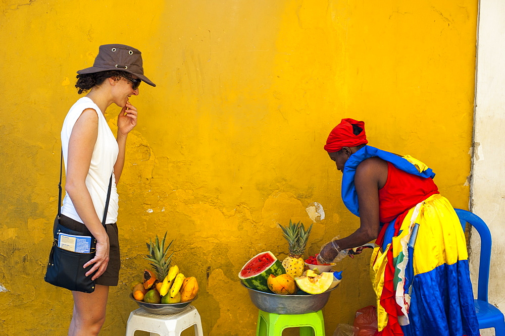 Woman dressed in traditional clothes cutting and selling fruit in the colorful old town of Cartagena, Colombia, South America