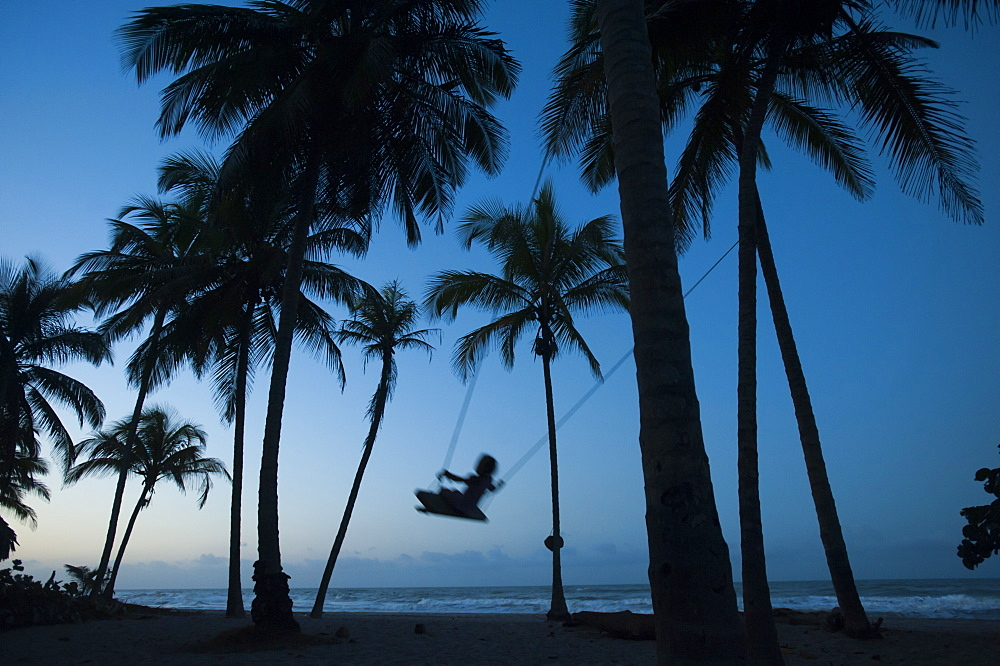 A girl plays on a swing tied between palm trees on the Carribean coast at Palomino in Colombia, South America