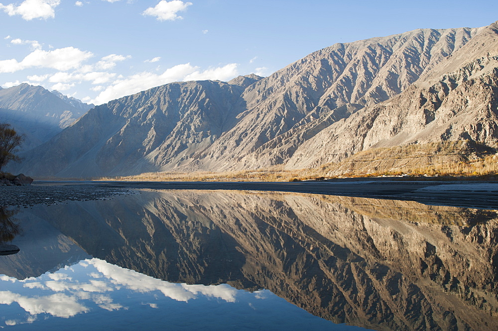 The crystal clear Shyok River creates a mirror image in the Khapalu valley near Skardu, Gilgit-Baltistan, Pakistan, Asia