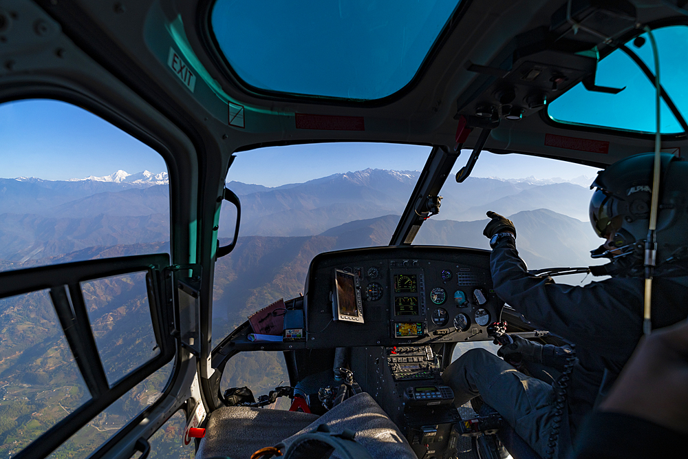 A helicopter flies towards the Himalayas as the pilot points towards the Ganesh Himal range through the window, Langtang region, Nepal, Asia