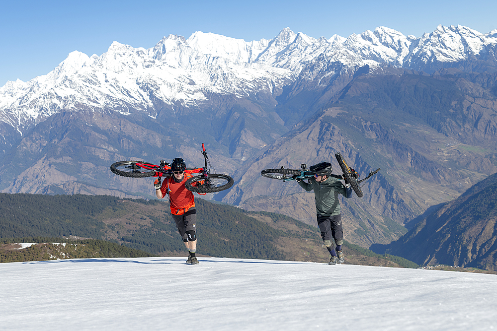 Mountain bikers carry their bikes up a snow covered slope in the Himalayas with views of the Langtang range in the distance, Nepal, Asia - 1225-1331