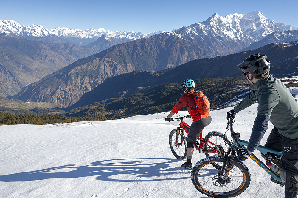 Mountain bikers descend a snow covered slope in the Himalayas with views of the Langtang range in the distance, Nepal, Asia - 1225-1332