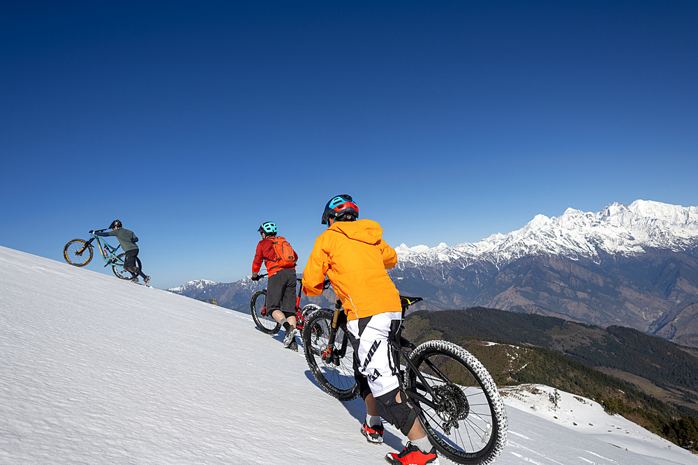 Mountain bikers cycle along a snow covered slope in the Himalayas with views of the Langtang range in the distance, Nepal, Asia