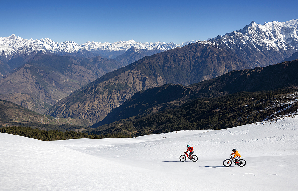Mountain bikers descend a snow covered slope in the Himalayas with views of the Langtang range in the distance, Nepal, Asia - 1225-1338