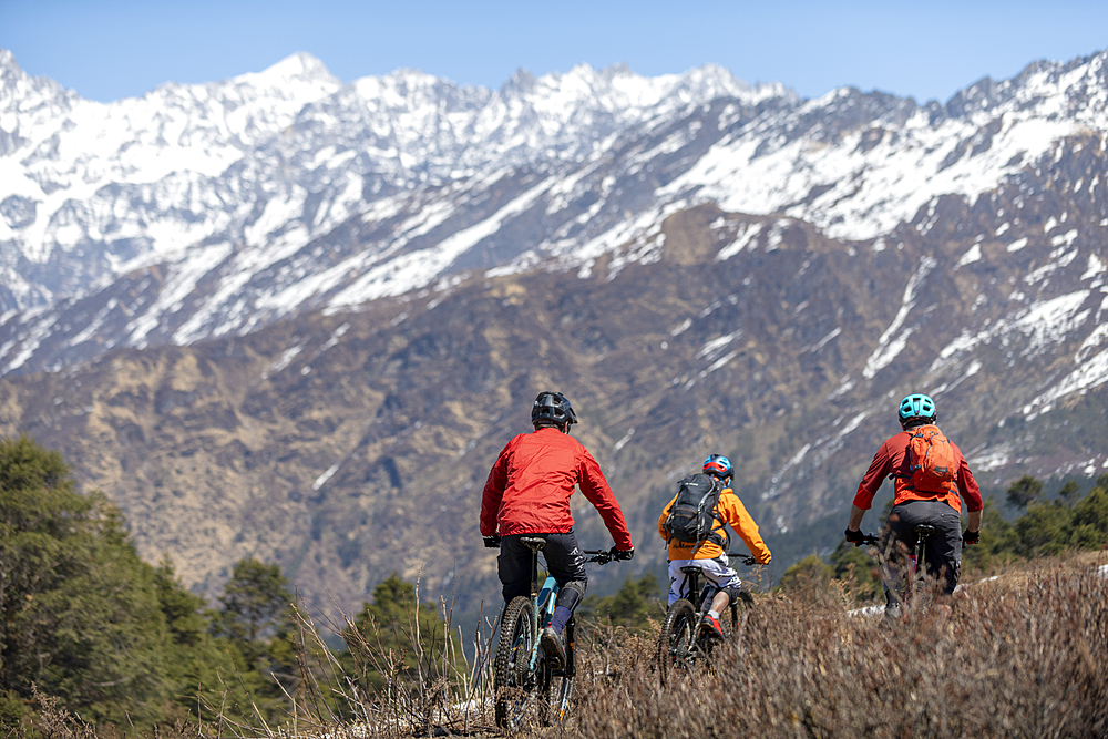 Mountain biking in the Himalayas with views of the Langtang mountain range in the distance, Nepal, Asia - 1225-1345