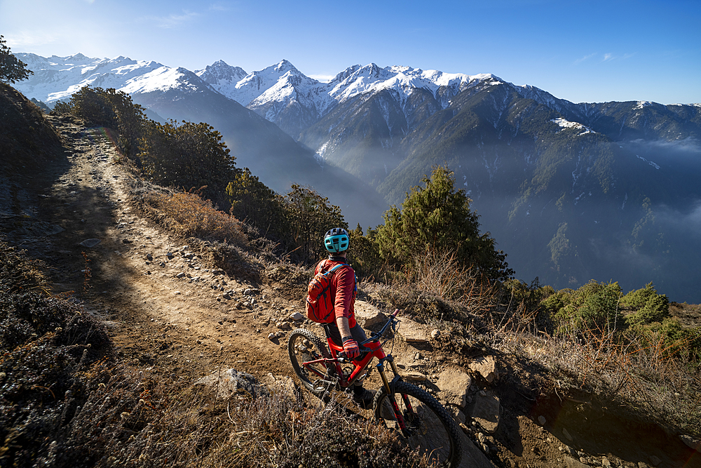 A mountain biker takes a rest on an Enduro style single track trail in the Nepal Himalayas near the Langtang region, Nepal, Asia - 1225-1350