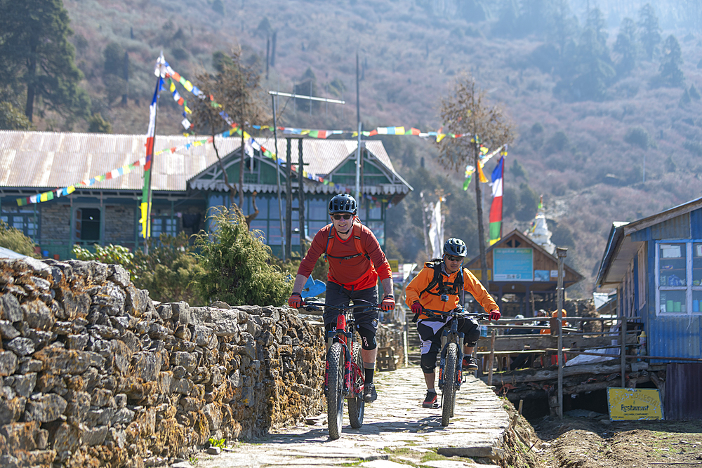 Mountain bikers in the little village of Sing Gompa in the Gosainkund region in the Himalayas, Langtang region, Nepal, Asia