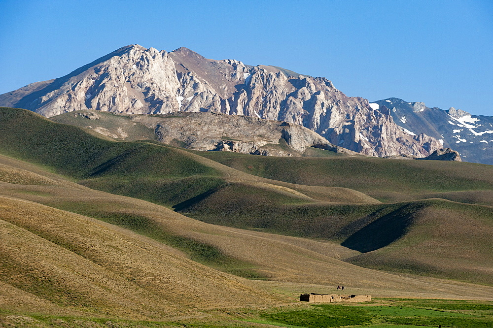 A distant house in the grasslands with views of mountains in the distance, Bamiyan province, Afghanistan, Asia