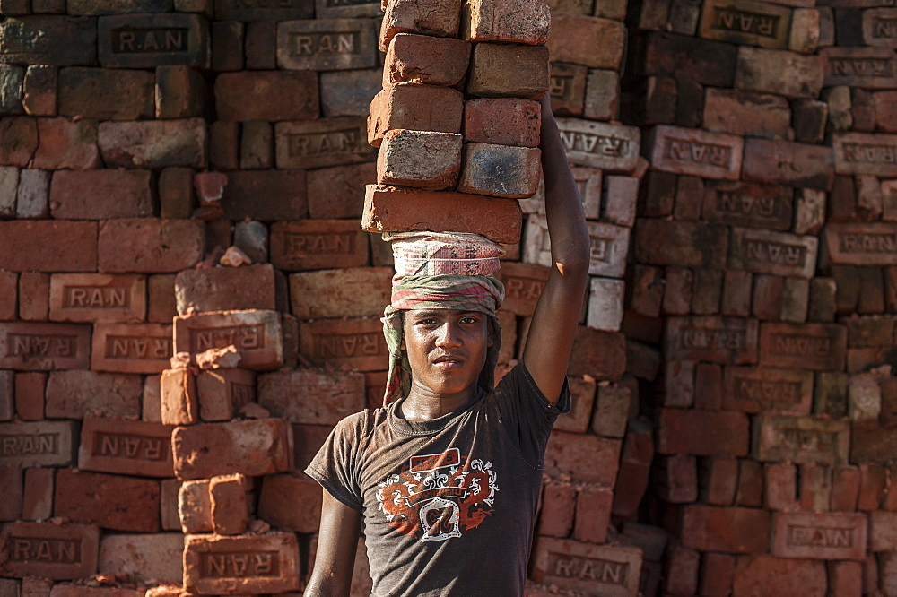 A young man carries up to 50 kilos of bricks by balancing them on his head, brick factory in Chittagong Hill Tracts, Bangladesh, Asia