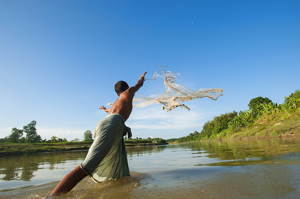 A man casts his net into the river in the Kharacharri district of the Chittagong Hill Tracts. Bangladesh, Asia