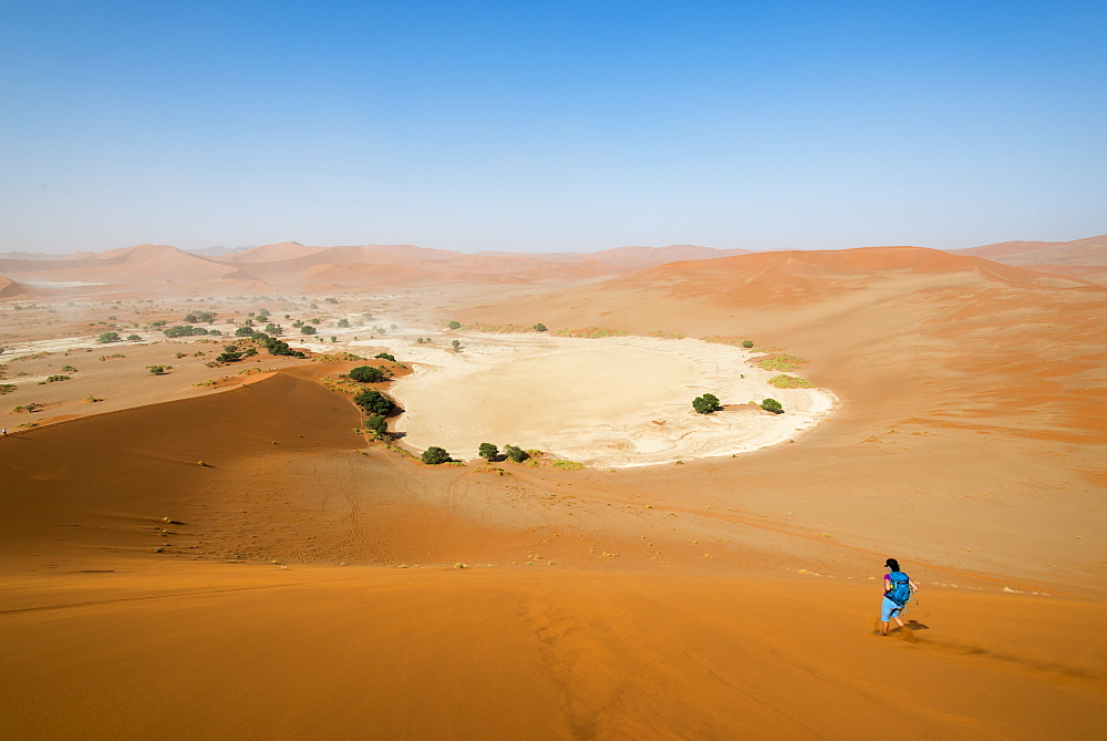 A woman runs down from the summit of Sossusvlei sand dune, Namibia, Africa