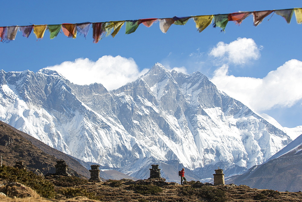 A trekker on their way to Everest Base Camp, Mount Everest is the peak to the left with some spindrift blowing from the top, Himalayas, Nepal, Asia