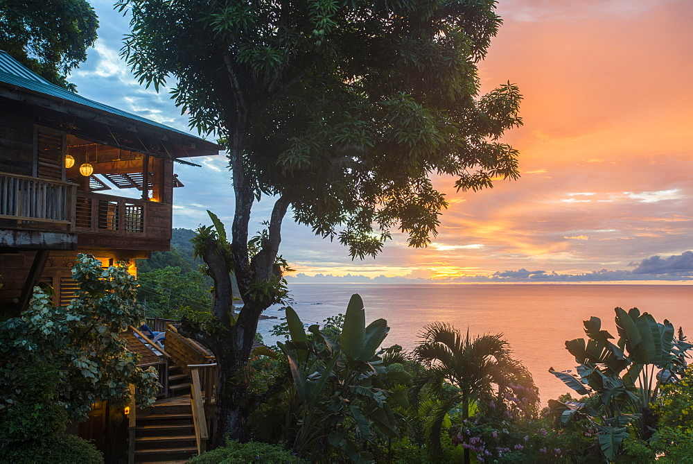 A tree house style apartment in the rainforest faces out to sea at sunset in Castara Bay in Tobago