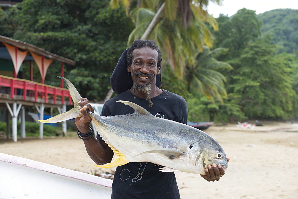 A man holds up a freshly caught Trevally fish at Castara in Tobago, Trinidad and Tobago, West Indies, Caribbean, Central America