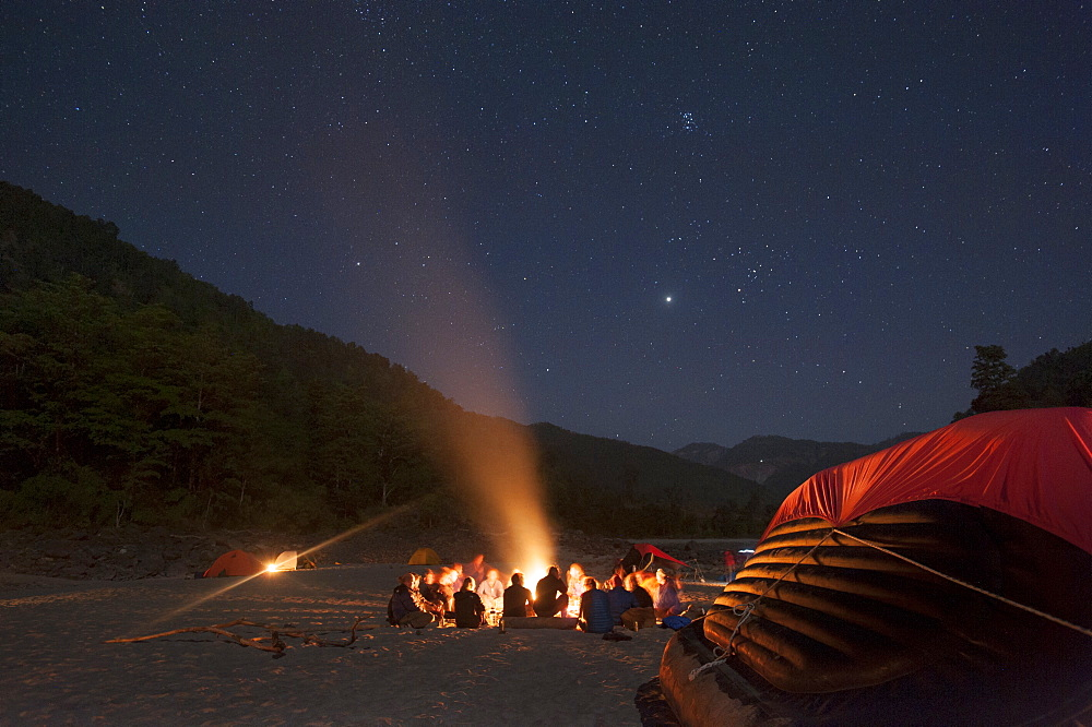 Sitting around a campfire next to the Karnali River during a rafting expedition in Nepal, Asia