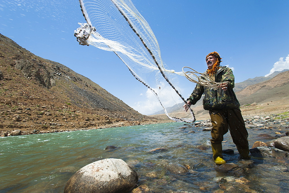 A man from the Panjshir Valley fishes with a throw-net, Afghanistan, Asia