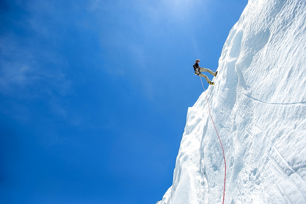 A climber makes her way down an ice wall in preparation for climbing Everest, Himalayas, Nepal, Asia