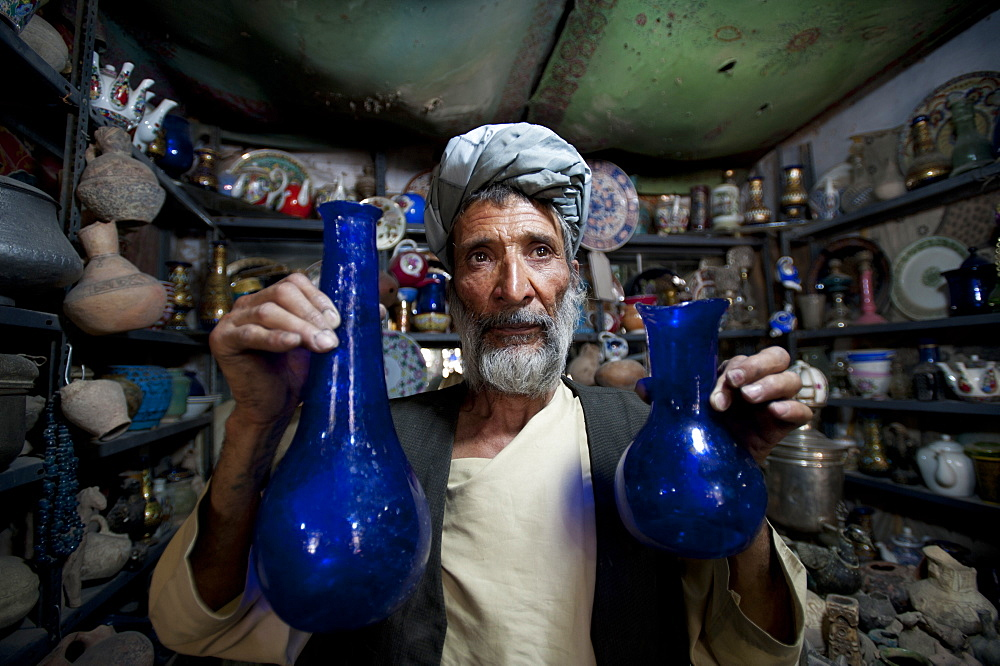 A glass blower holds up blue glass gourd-shaped vases in a trinket shop in Herat, Afghanistan, Asia