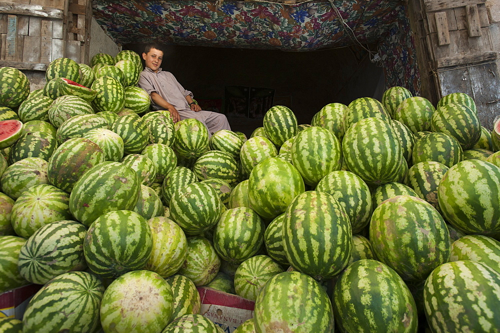 A boy in a market rests on a giant pile of water melons, Herat, Afghanistan, Asia