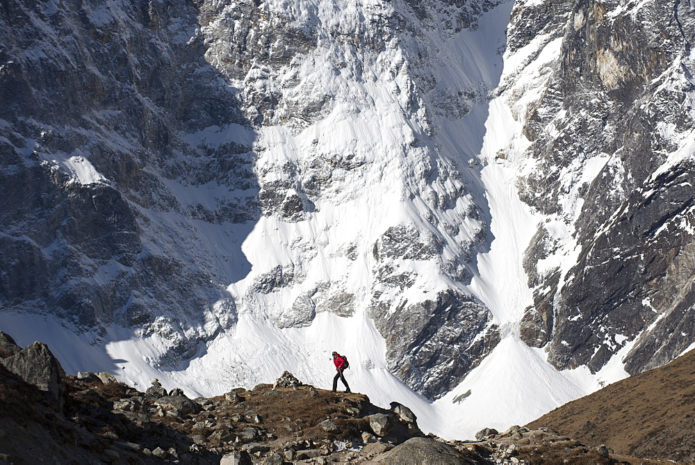 A trekker in the Everest region on the way up to Everest base camp seen here walking in front of Cholatse in Nepal