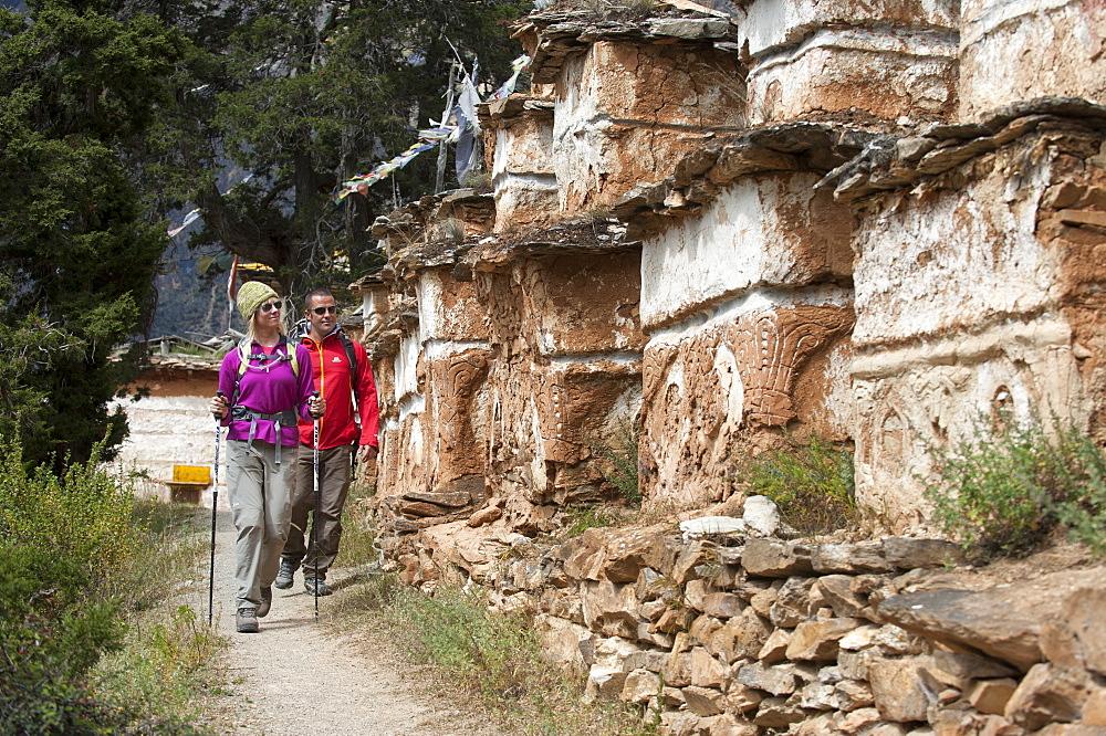 Trekking past a line of Tibetan chortens near Phoksundo lake in Dolpa, a remote region of Nepal, Asia