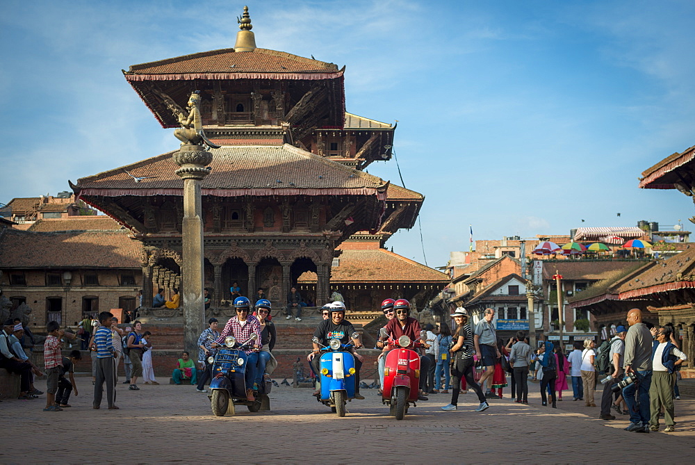 A group of tourists sit with their scooters in the historical temple square in Patan in Kathmandu in Nepal