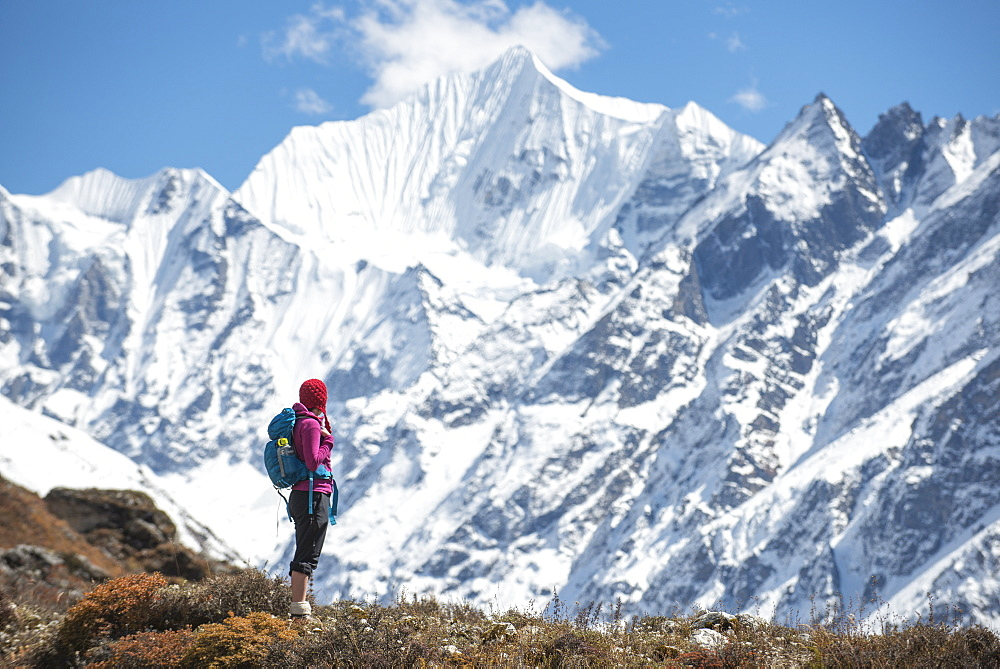 A woman trekking in the Langtang valley in Nepal with a view of Ganchempo in the distance