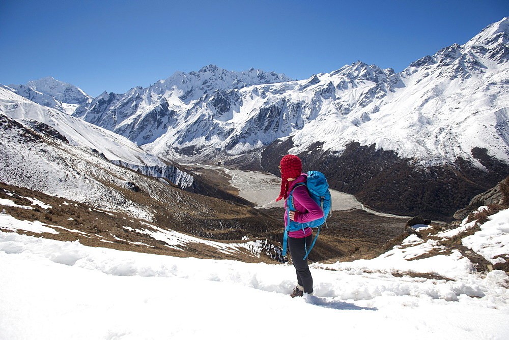 A girl surveys the Langtang valley in Nepal from the top of Kyanjin Ri with the peak of Ganchempo far in the distance at the hea