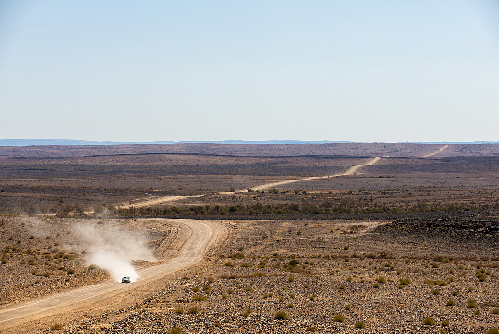 A car leaves a cloud of dust as it apporachs along the long dusty road from the Fish River Canyon, Namibia, Africa