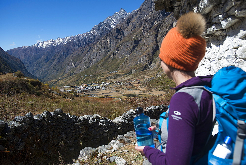 A woman trekking in the Langtang valley in Nepal rests near a chorten and take in the view.