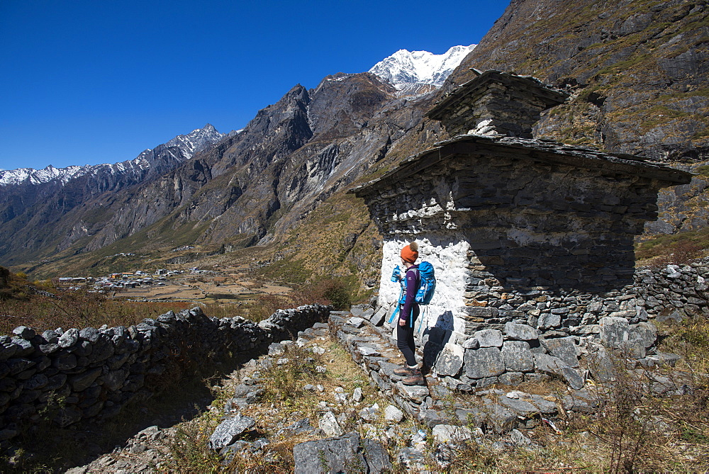 A woman trekking in the Langtang valley rests near a chorten, Langtang Region, Himalayas, Nepal, Asia