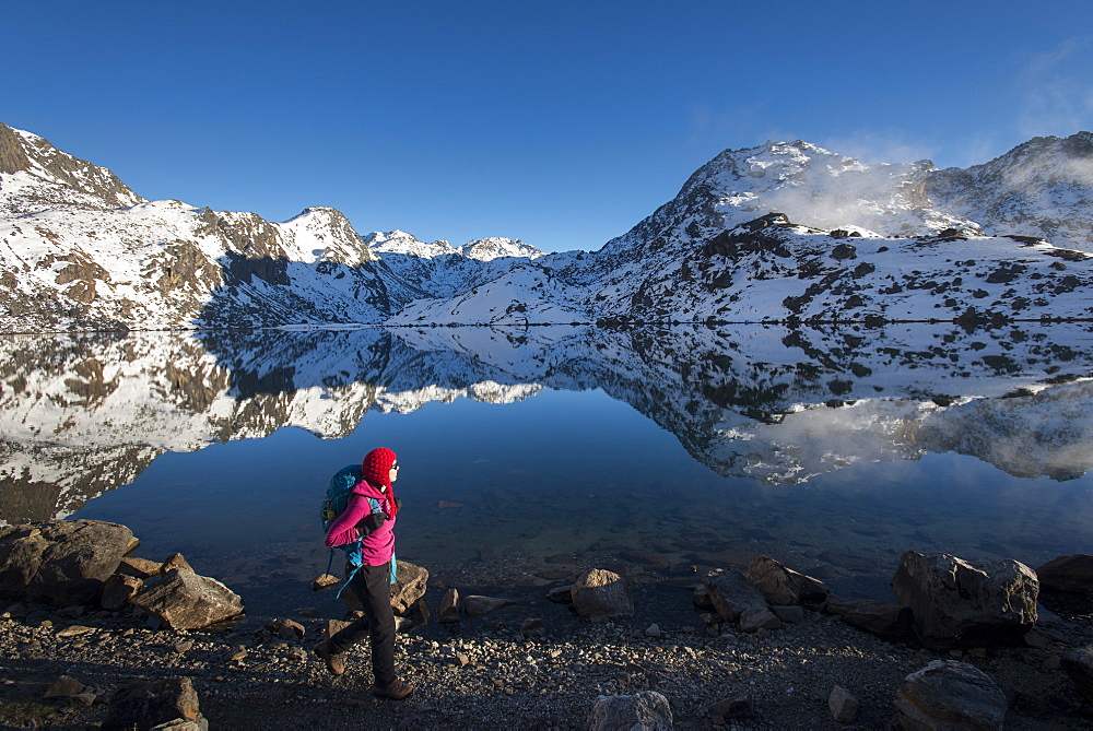 A woman walks past the holy lake of Gosainkund in the Langtang region of Nepal