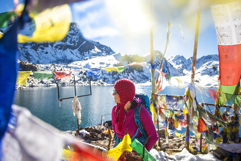 A trekker stands among prayer flags beside the holy lakes at Gosainkund in the Langtang region, Himalayas, Nepal, Asia