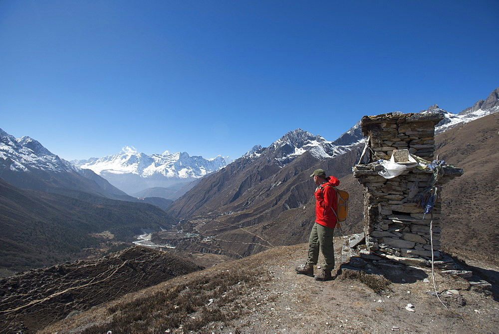 A trekker in the Everest region looks down on the Khumbu Valley towards Pangboche, Khumbu Region, Himalayas, Nepal, Asia