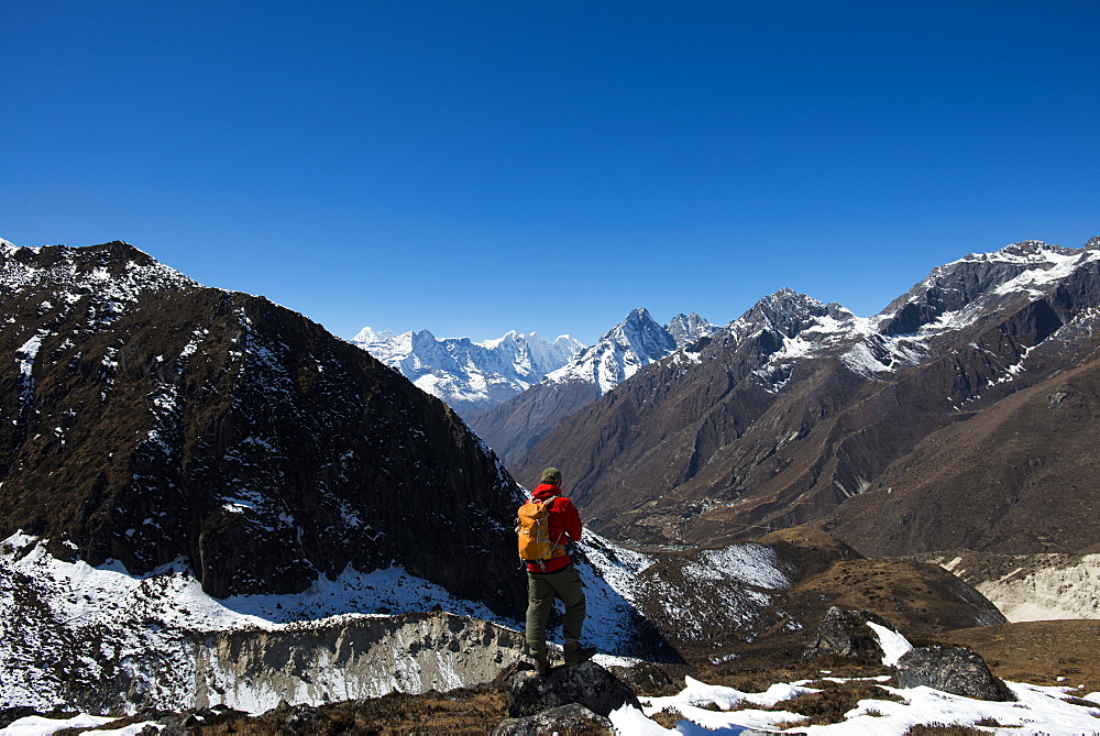 A trekker in the Everest region of Nepal looks down on the Khumbu valley towards Pangboche.