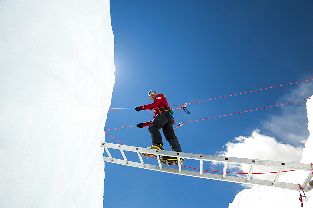 A climber on Everest makes his way across a crevasse using a temporary ladder, Khumbu Region, Nepal, Asia