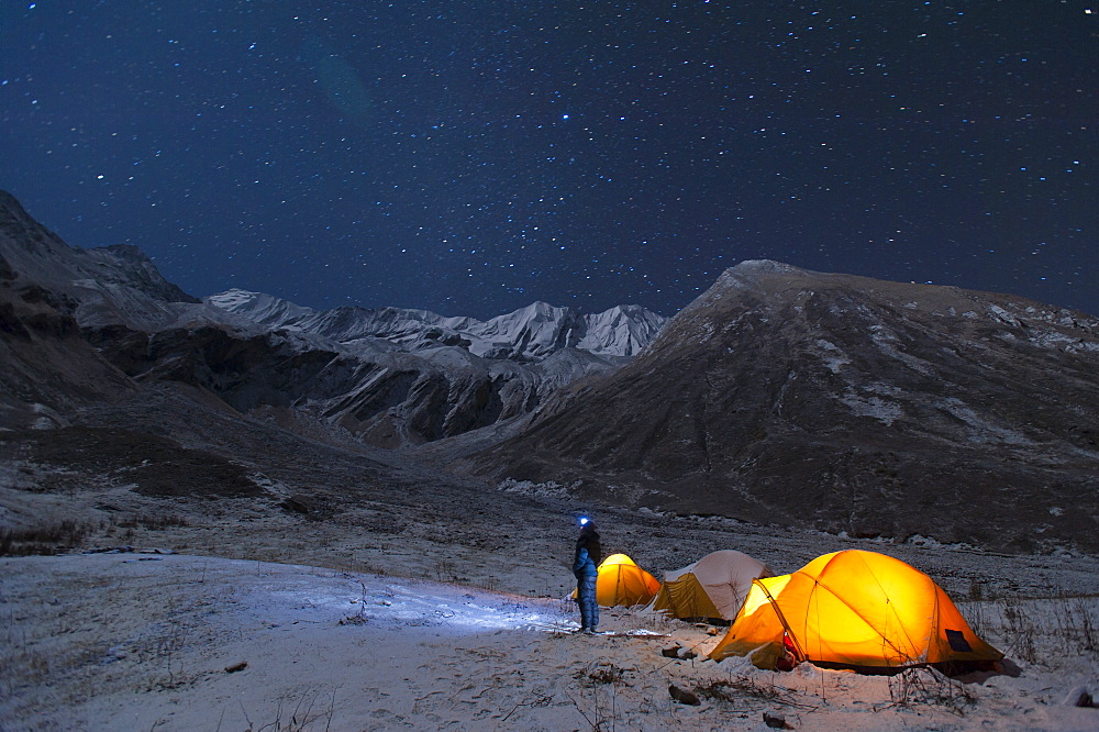 A man stands outside his tent to look at the stars in the little explored Juphal Valley in the remote Dolpa region of Nepal, Himalayas, Nepal, Asia