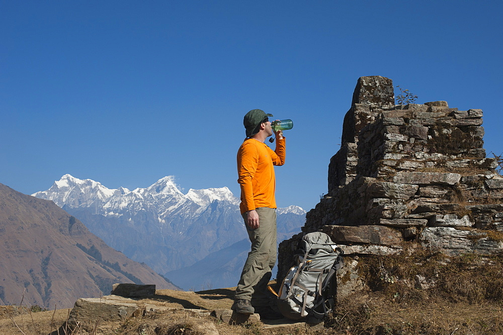 A trekker takes some well earned refreshment during the Manaslu circuit trek, Himalayas, Nepal, Asia