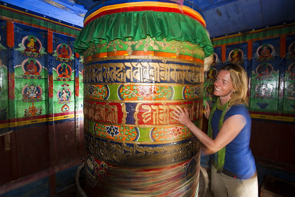 A trekker spins a Buddhist prayer wheel while trekking towards to Everest Base Camp, Khumbu Region, Nepal, Asia