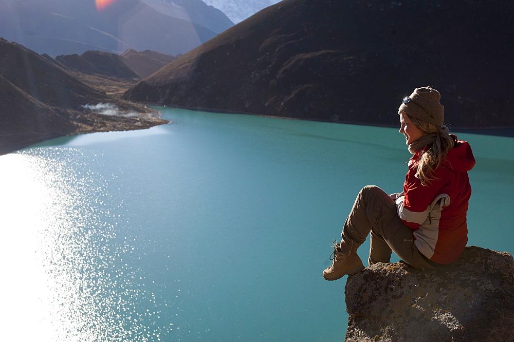 A trekker in the Everest region stops half way up Goyko Ri to enjoy the views, Khumbu Region, Nepal, Asia