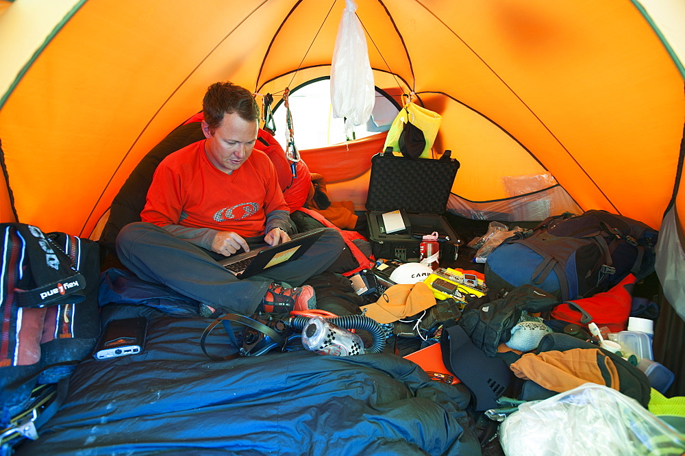 An Everest expeditioner sits among his mountain of equipment while he checks his email with a satelite modem, Khumbu Region, Nepal, Asia