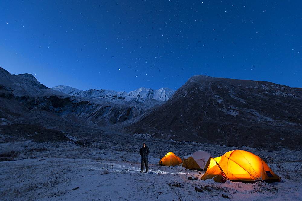 A man standing outside his tent on a cold night in the little explored Juphal Valley in the remote Dolpa region, Nepal, Asia