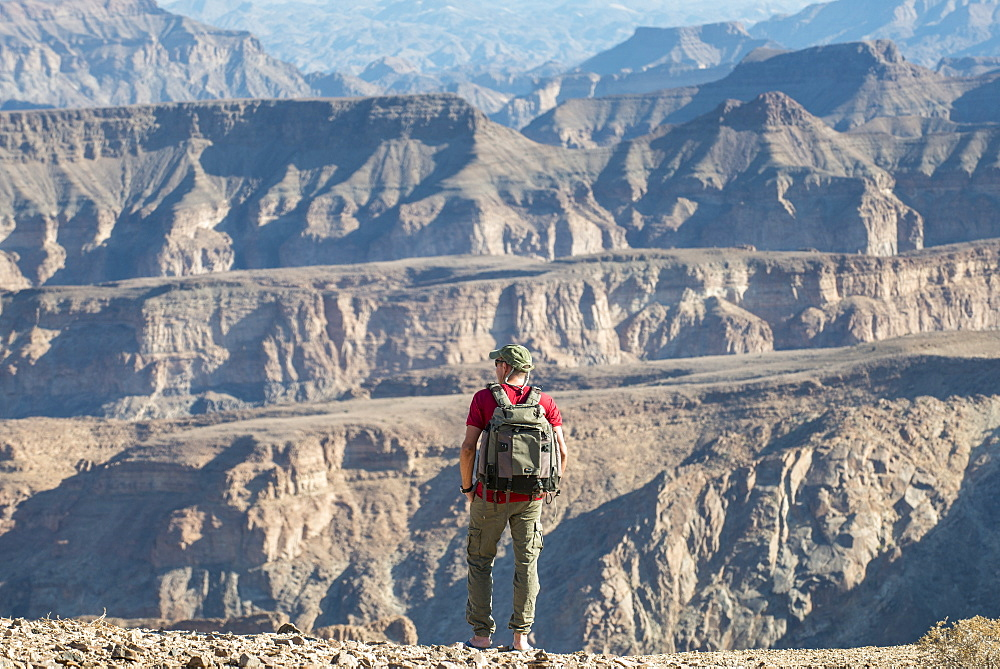 A man stands on the edge of the Fish River Canyon, Namibia, Africa