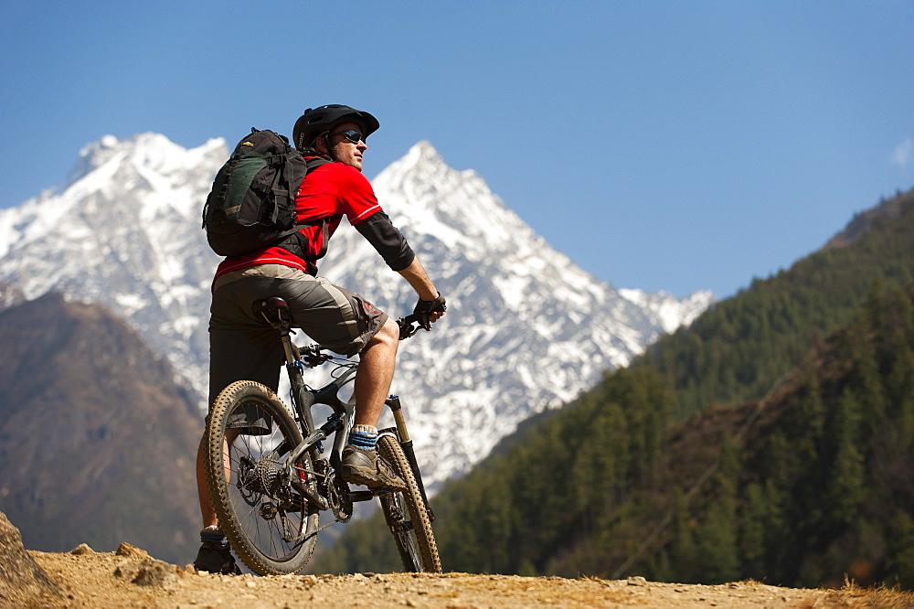 A mountain biker in the Tsum Valley looks at Ganesh Himal mountains, Manaslu region, Himalayas, Nepal, Asia