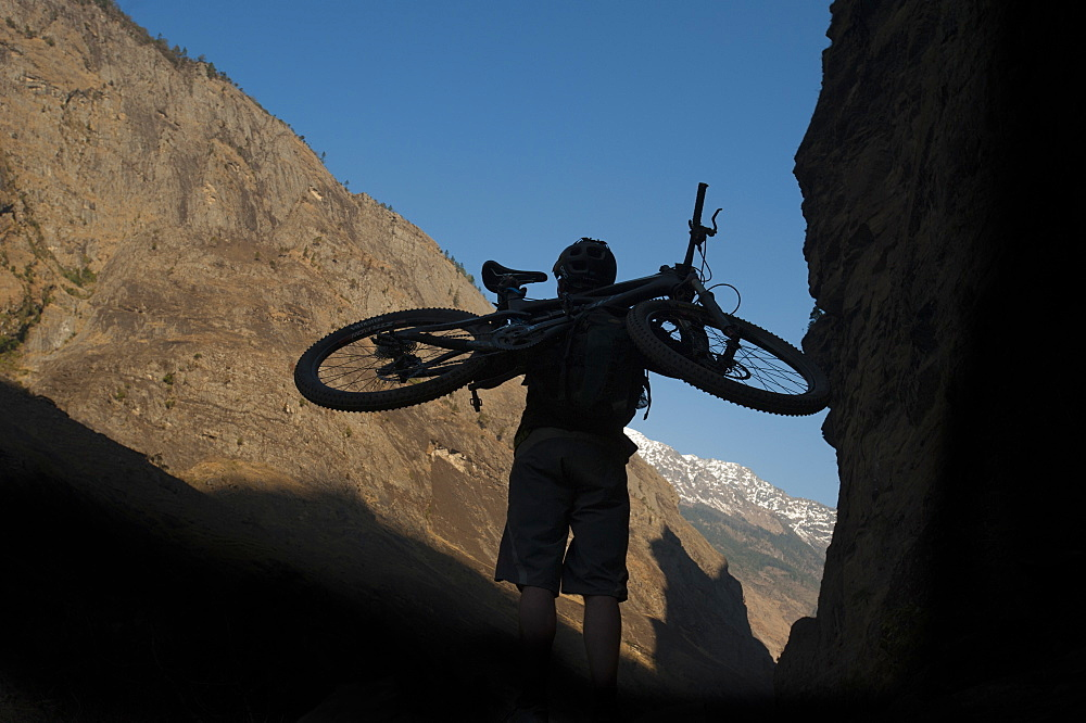 A mountain biker carries his bike into the Himalayas, Nepal, Asia