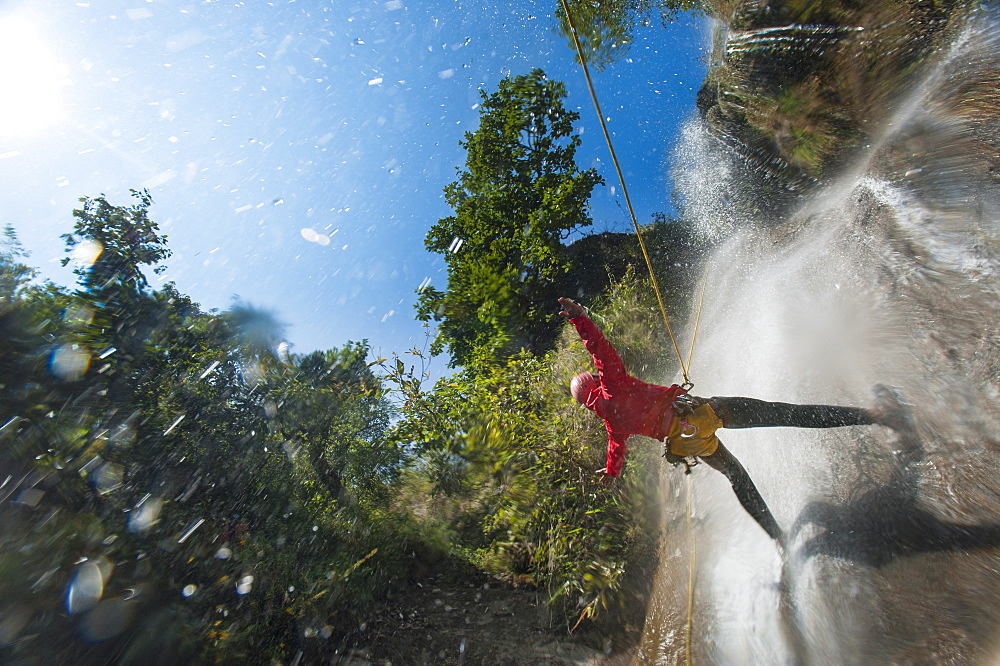 A man pauses to hold his arms in the falling water while canyoning in Nepal, Asia