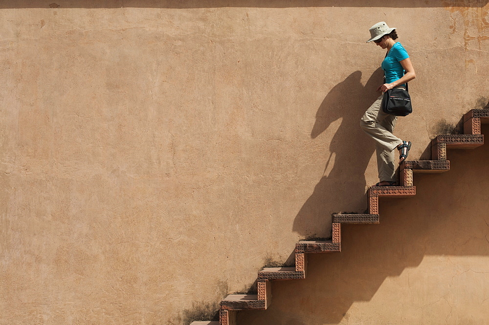 A tourist climbs downs some exposed steps within the Fatehpur Sikri temple complex in India