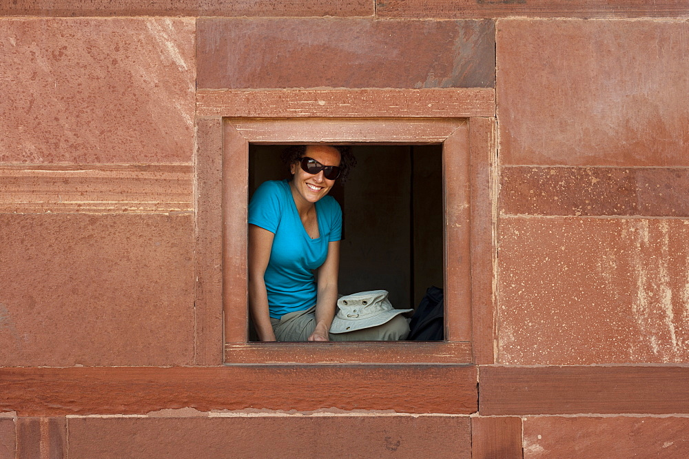 A tourist peeks out from one the windows within the Fatehpur Sikri temple complex in India