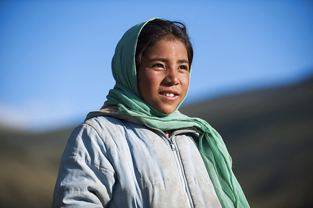 A nomad girl in Ladakh in India smiles as her father comes home from the hills